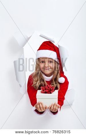 Happy little girl with christmas present - leaning through hole in paper layer