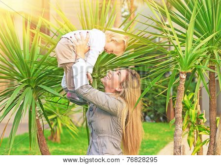 Cheerful mother playing with baby in fresh green palm park, smiling woman lifting up her cute little daughter, happy young family concept