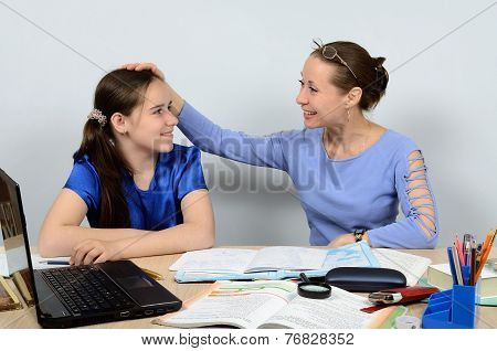 Gracious teacher praises and pats on the head with a good pupil girl