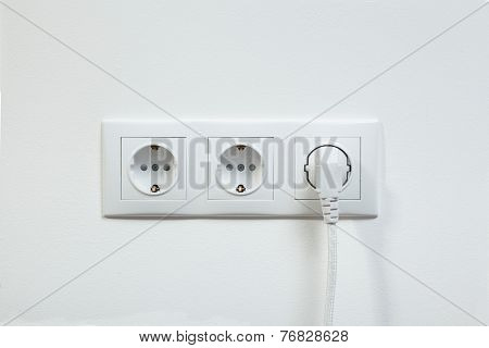Close up photo of a white power plug plugged in a triple electric socket