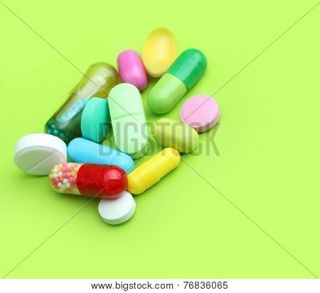 Various pharmaceuticals, pills on green background.