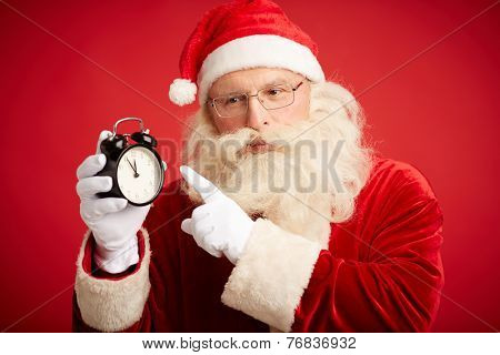 Pensive Santa Claus with alarm clock pointing at it