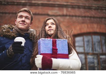 Portrait of pretty girl with giftbox and young man with plastic glass of coffee outdoors