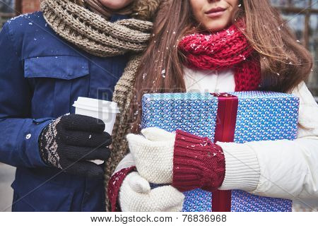 Close-up of girl with giftbox and her boyfriend with plastic glass of coffee outdoors