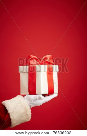 Santa Claus gloved hand holding giftbox with red bow