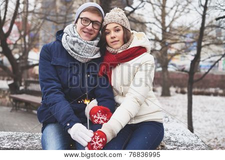 Amorous boyfriend and girlfriend with Bengal light celebrating Valentine�?�¢??s Day outside