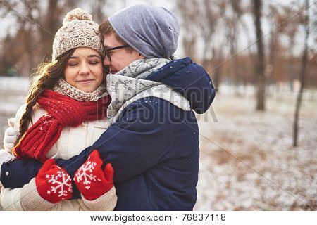 Happy man embracing his girlfriend outdoors