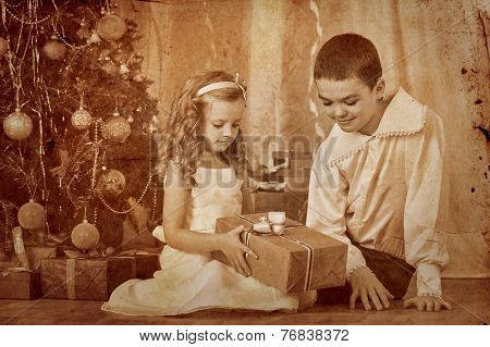 Happy children  receiving gifts under Christmas tree.