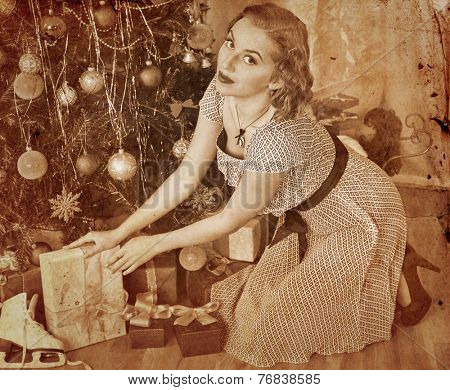 Woman receiving gifts under Christmas tree. Sepia toned.