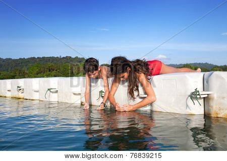 Young boy and  his sister catching tiny prawns while they were on floating platform on tropical island