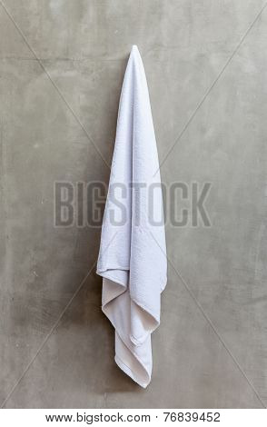 Hanging White Towel Draped On Exposed Concrete Wall In The Bathroom.