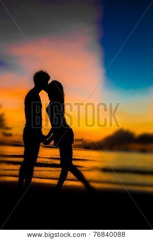 silhouettes of young loving couple on bright sunset sky and sea background