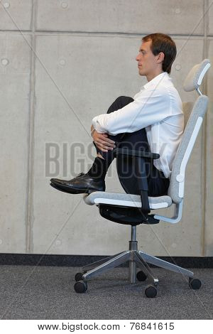 business man in knee to chest position on office chair