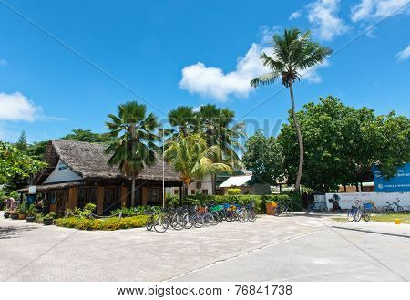 LA DIGUE, SEYCHELLES - 21 OCTOBER 2014 - Thatched roofed buildings with a row of bicycles parked at La Digue harbor, Seychelles surrounded by palm trees and tropical vegetation on 21 October 2014