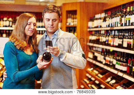 Man taking picture of wine bottle in supermarket with his smartphone