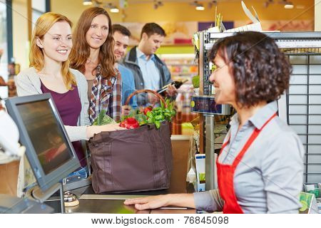 Woman with groceries waiting in line at the supermarket checkout