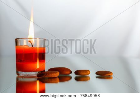 Spa candle light on glass with stone