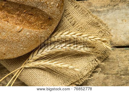 Fresh Bread With Wheat Ears On Wooden Table.