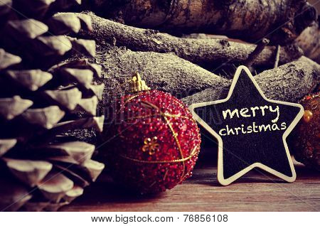 the text merry christmas written in a star-shaped blackboard, and some christmas ornaments, and pinecones and a pile of logs in the background