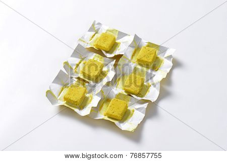 six cubes of herb instant broth with paper wrappers