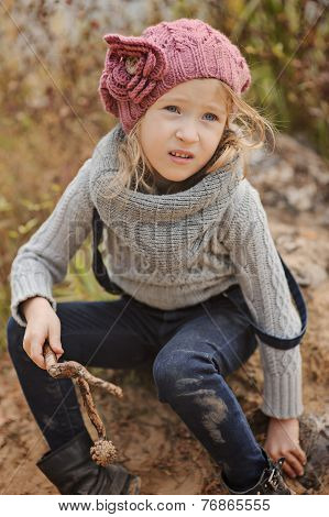 Cute child girl in knitted hat and sweater in autumn day
