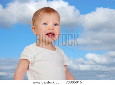 Blond baby with blue eyes with a beautiful sky of background