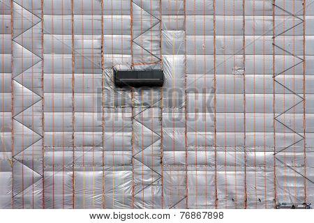 Scaffolding with plastic tarpaulin