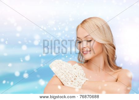 heath, people and beauty concept - beautiful young woman with bare shoulders washing herself over blue sky, snow and clouds background