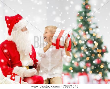 holidays, childhood and people concept - smiling little boy, santa claus with gifts over living room, christmas tree and snow background