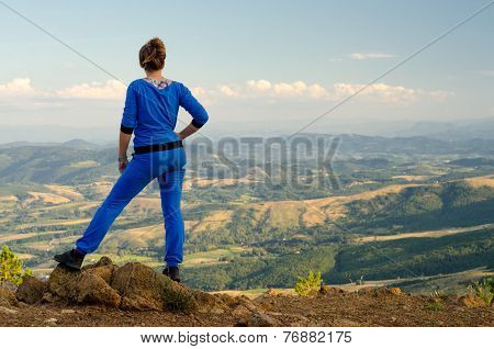 Teenage girl enjoying the view on top of the mountain