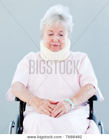 Upset Senior Woman With A Neck Brace Sitting On A Wheelchair