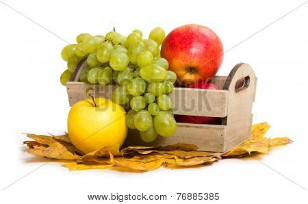 apples and grape in crate on autumn leaves background