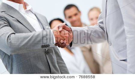 Businessmen Shaking Hand In Front Of Their Colleagues