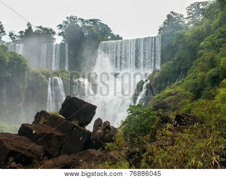 Iguazu Falls Framed By Rocks And Foliage