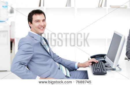 Smiling Young Businessman Working At A Computer