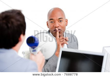 Afro-american Businessman Asking For Silece While His Colleague Yelling Through A Megaphone