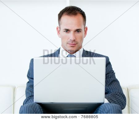 Concentrated Businessman Using A Laptop Sitting On A Sofa
