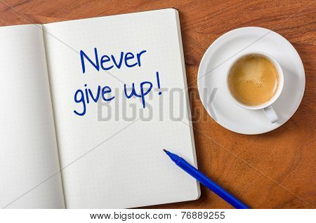 Notebook on a desk - Never give up