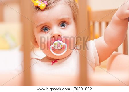 Little Girl Sitting In A Crib With