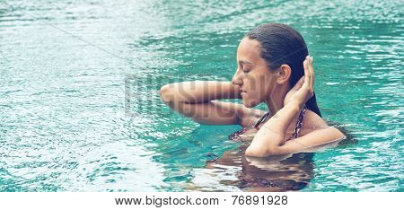 Young Asian woman enjoying a tranquil moment in a blue swimming pool standing with her hands raised to her wet hair and eyes closed as she meditates in the summer sunshine, with copyspace