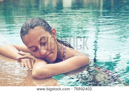 Contemplative young Asian woman in a sparkling blue swimming pool resting her head on her arms on the pool surround with closed eyes