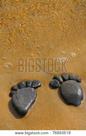 pair trace feet made of a pebble stone on the sea sand,  texture surface top view backdrop
