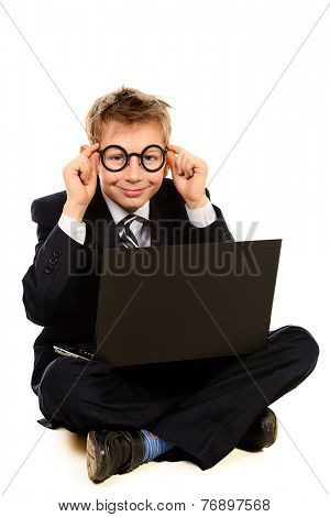 Portrait of a smart boy in a suit and glasses sitting with his laptop. Isolated over white.