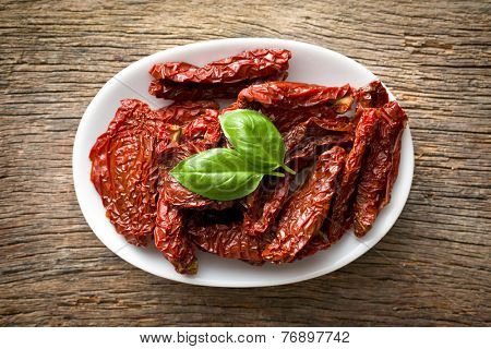 sun dried tomatoes and basil on wooden table