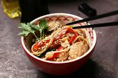 image of chinese wok  - Chinese noodles with vegetables and seafood in bowl and wok on wooden background - JPG