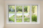 stock photo of four  - Large four pane window looking on summer backyard with pool and garden - JPG