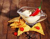 stock photo of nachos  - Tasty nachos and bowl with sauce on wooden background - JPG