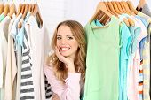 stock photo of racks  - Beautiful young woman near rack with hangers - JPG