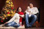 stock photo of new years baby  - Closeup portrait of cute cheerful family near Christmas tree at home - JPG