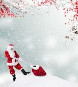 picture of snowy hill  - Santa Claus carrying gift sack on snowy hill - JPG
